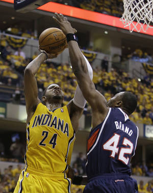 Photo - Indiana Pacers' Paul George (24) shootsagainst Atlanta Hawks' Elton Brand during the second half in Game 1 of an opening-round NBA basketball playoff series on Saturday, April 19, 2014, in Indianapolis. Atlanta defeated Indiana 101-93. (AP Photo/Darron Cummings)