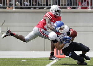 Photo - Ohio State cornerback Armani Reeves, left, knocks the ball away from Buffalo wide receiver Alex Neutz during the second quarter of an NCAA college football game Saturday, Aug. 31, 2013, in Columbus, Ohio. (AP Photo/Jay LaPrete)