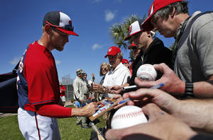 Photo - Washington Nationals starting pitcher Stephen Strasburg signs autographs after a spring training baseball workout, Thursday, Feb. 20, 2014, in VIera, Fla. (AP Photo/Alex Brandon)