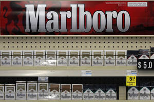 Photo - FILE - In this Wednesday, July 17, 2013 file photo, Marlboro cigarettes are on display in a CVS store in Pittsburgh. The nation's second-largest drugstore chain says it will phase out cigarettes, cigars and chewing tobacco by Oct. 1 as it continues to focus more on health care. The move will cost the Woonsocket, R.I., company about $2 billion in annual revenue. (AP Photo/Gene J. Puskar, File)