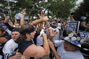 Photo -   Penn State University linebacker Michael Mauti, second from left foreground, and his teammates are greeted by a pep rally of supporters on the way to a morning workout outside the Lasch Football building on the Penn State main campus in State College, Pa., Tuesday, July 31, 2012. (AP Photo/Gene J. Puskar)