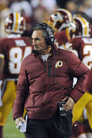 Photo - In this Sunday, Jan. 6, 2013, photo, Washington Redskins coach Mike Shanahan watches during the first half of an NFL wild card playoff football game against the Seattle Seahawks in Landover, Md. Shanahan has come under fire in the wake of Robert Griffin III reinjuring his right knee in Sunday's 24-14 wild-card loss to Seattle. The criticism has ranged from whether Shanahan cared enough for his sensational rookie to whether the natural protocol for dealing with injuries was followed. (AP Photo/Richard Lipski)