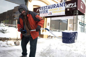 Photo - Tom Sheridan, LaSalle Grill's executive chef, shoves a path to the street from the sidewalk outside of the restaurant on Monday, Jan. 27, 2014, in downtown South Bend, Ind. Sub-freezing temperatures and blowing snow returned to the Michiana area yet again as the City of South Bend declared a winter weather emergency. (AP Photo/South Bend Tribune, James Brosher)