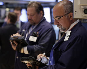 Photo - In this Tuesday, Aug. 13, 2013 photo, trader John Santiago, left, and John Liotti work on the floor of the New York Stock Exchange. Wall Street appears headed for a lower opening Wednesday, Aug. 21, 2013, based on futures trading. (AP Photo/Richard Drew)