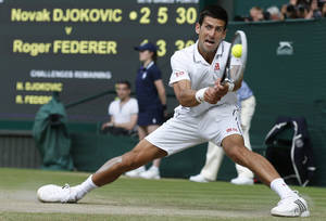 Photo - Novak Djokovic of Serbia watches the ball hit his racquet as he plays a return to Roger Federer of Switzerland during their men's singles final match at the All England Lawn Tennis Championships in Wimbledon, London, Sunday, July 6, 2014. (AP Photo/Sang Tan, Pool)