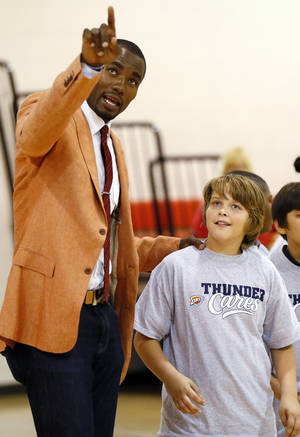 photo - Serge Ibaka of the Oklahoma City Thunder NBA basketball team gives a shooting tip to Tyler Capps, 12, at the Boys and Girls Club of Oklahoma County, Monday, Sept. 10, 2012. Before interacting with children at the club, Ibaka held a press conference to discuss his staying with the Thunder under a new contract. Photo by Nate Billings, The Oklahoman