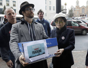 "Photo - Sean Lennon and Yoko Ono help deliver boxes of comments to the New York State Department of Environmental Conservation on its proposed natural gas drilling regulations on Friday, Jan. 11, 2013, in Albany, N.Y. Environmental, health and community groups opposed to shale gas drilling and hydraulic fracturing, or ""fracking,"" say they collected more than 200,000 comments during an intense 30-day effort featuring online coaching and comment-writing workshops at churches, community centers, food co-ops, coffee shops and holiday house parties from New York City to Buffalo. (AP Photo/Mike Groll)"