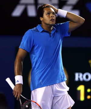 Photo - Jo-Wilfried Tsonga of France reacts after losing a point during his fourth round match against Roger Federer of Switzerland at the Australian Open tennis championship in Melbourne, Australia, Monday, Jan. 20, 2014. (AP Photo/Aaron Favila)