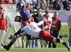 Photo -   South Dakota defensive back Aaron Swift (9) tackles Northwestern quarterback Kain Colter (2) during the first half of an NCAA college football game in Evanston, Ill., Saturday, Sept. 22, 2012. (AP Photo/Nam Y. Huh)