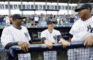 Photo - New York Yankees pitcher Masahiro Tanaka, center, talks with teammates pitcher CC Sabathia, left, and pitcher Ivan Nova, right, before an exhibition baseball game against the Pittsburgh Pirates Thursday, Feb. 27, 2014, in Tampa, Fla. (AP Photo/Charlie Neibergall)