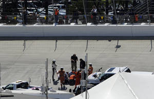 Photo - Workers and officials repair the track surface during the NASCAR Sprint Cup series auto race, Sunday, June 1, 2014, at Dover International Speedway in Dover, Del. (AP Photo/Nick Wass)