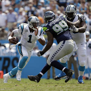 Photo - Carolina Panthers quarterback Cam Newton (1) runs past Seattle Seahawks defensive tackle Tony McDaniel (99) being blocked by Carolina Panthers' Edmund Kugbila (70) during the first half of an NFL football game in Charlotte, N.C., Sunday, Sept. 8, 2013. (AP Photo/Bob Leverone)