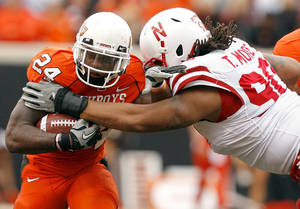 Photo - OSU's Kendall Hunter gets past Nebraska's Terrence Moore during the college football game between the Oklahoma State Cowboys (OSU) and the Nebraska Huskers (NU) at Boone Pickens Stadium in Stillwater, Okla., Saturday, Oct. 23, 2010. Photo by Sarah Phipps, The Oklahoman