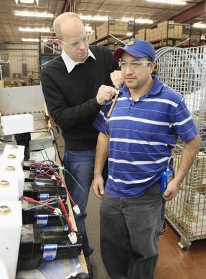 Photo - Jason Young, assistant director of industrial hygiene with the Oklahoma Department of Labor, attaches a device to capture the surrounding breathing zone air to Leo Rodas, assembler for Wellmark, inside the Wellmark manufacturing plant in Oklahoma City. Photo by Paul B. Southerland, The Oklahoman