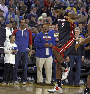 Photo - Miami Heat's LeBron James (6) ceebrates after the defeat of the Golden State Warriors at the end of an NBA basketball game Wednesday, Feb. 12, 2014, in Oakland, Calif. (AP Photo/Ben Margot)