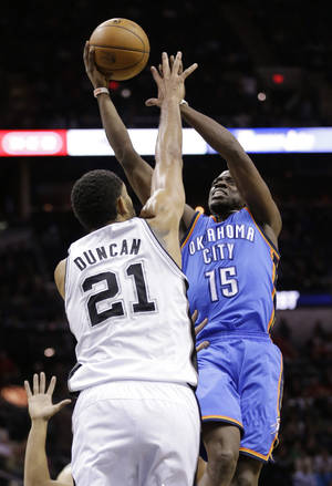 Photo - Oklahoma City Thunder's Reggie Jackson (15) shoots over San Antonio Spurs' Tim Duncan (21) during the second half of an NBA basketball game, Wednesday, Jan. 22, 2014, in San Antonio. The Thunder won 111-105. (AP Photo/Eric Gay)