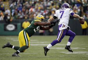 Photo - Minnesota Vikings' Christian Ponder tries to get away from Green Bay Packers' Datone Jones during the second half of an NFL football game Sunday, Nov. 24, 2013, in Green Bay, Wis. (AP Photo/Mike Roemer)