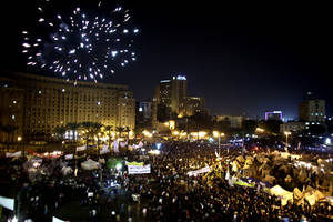 photo - Fireworks burst over Tahrir Square as protesters gather in Cairo, Egypt, Tuesday, Dec. 4, 2012. A protest by tens of thousands of Egyptians outside the presidential palace in Cairo turned violent on Tuesday as tensions grew over Islamist President Mohammed Morsi's seizure of nearly unrestricted powers Thousands of protesters also gathered in Cairo's downtown Tahrir Square, miles away from the palace, to join several hundred who have been camping out there for nearly two weeks. (AP Photo/Maya Alleruzzo)