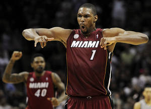 Photo - Miami Heat's Chris Bosh (1) yells after scoring the winning basket during the second half of an NBA basketball game against the San Antonio Spurs, Sunday, March 31, 2013, in San Antonio. Miami won 88-86. (AP Photo/Darren Abate)