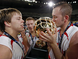 Photo - Forgan's Tyler McReynolds, right, kisses the gold ball trophy next to teammates Tanner Jones, left, and Tayler Eagan, center, after winning the Class B state championship game Saturday at State Fair Arena.  Photo by Nate Billings, The Oklahoman