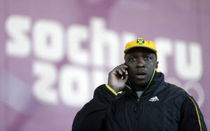 Photo - Winston Watts, the driver for JAM-1 of Jamaica, speaks on the phone after arriving at the sliding center during a training session for the men's two-man bobsled at the 2014 Winter Olympics, Wednesday, Feb. 5, 2014, in Krasnaya Polyana, Russia. Watts and his team were unable to practice because the Jamaican team equipment and luggage did not arrive in Sochi.  (AP Photo/Natacha Pisarenko)