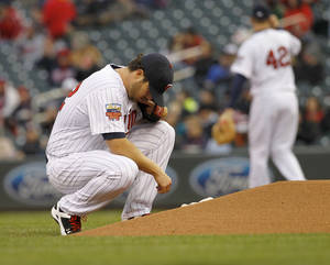 Photo - Minnesota Twins pitcher Phil Hughes kneels behind the mound before delivering to the Toronto Blue Jays during the first inning of the MLB American League  baseball game in Minneapolis, Tuesday, April 15, 2014.  (AP Photo/Ann Heisenfelt)