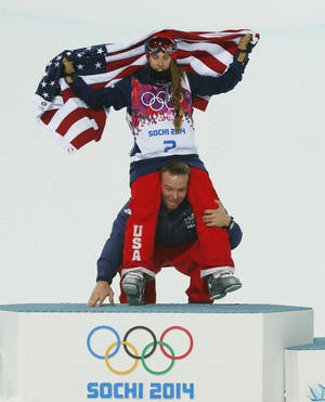 Photo - David Wise of the United States, the men's halfpipe gold medal winner, picks up Maddie Bowman of the United States after she won the gold medal in the women's ski halfpipe final, at the Rosa Khutor Extreme Park, at the 2014 Winter Olympics, Thursday, Feb. 20, 2014, in Krasnaya Polyana, Russia.(AP Photo/Sergei Grits)
