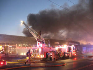 Photo - Firefighters combat a machine shop blaze  Sunday. Photo by MATT DINGER, The Oklahoman