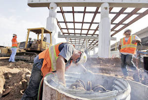 photo - Enrico Dias, center, cuts metal as he works on the Interstate 244 bridge just west of the Arkansas River last week. Photo by MIKE SIMONS, Tulsa World