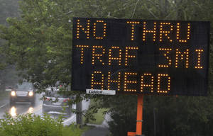 Photo - An electronic sign in West Tisbury, Mass., on the island of Martha's Vineyard flashes an advisory Friday, Aug. 9, 2013 to motorists of upcoming road closures. The planned road closures, scheduled to begin Saturday, Aug. 10 and continue through Sunday, Aug. 18, 2013, coincide with President Barack Obama's visit to the island. (AP Photo/Steven Senne)