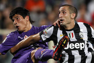 Photo -   Fiorentina's Facundo Roncaglia, left, is challenged by Juventus defender Giorgio Chiellini during a Serie A soccer match between Juventus and Fiorentina, at the Artemio Franchi stadium in Florence, Italy Tuesday, Sept. 25, 2012. (AP Photo/Fabrizio Giovannozzi)