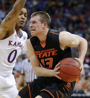 Photo - Oklahoma State's Phil Forte, right, looks to shoot beside Kansas' Frank Mason during Thursday's game. Forte scored 16 points as the Cowboys lost 77-70 in overtime.