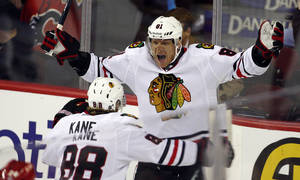 Photo - Chicago Blackhawks' Marian Hossa, right, from Slovakia, celebrates his goal with teammate Patrick Kane during overtime of an NHL hockey game in Calgary, Alberta, Saturday, Feb. 2, 2013. The Blackhawks defeated the Flames 3-2 in a shootout. (AP Photo/The Canadian Press, Jeff McIntosh)