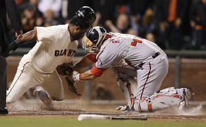 Photo - Washington Nationals catcher Wilson Ramos, right, tags out San Francisco Giants' Pablo Sandoval in the sixth inning of a baseball game Tuesday, June 10, 2014, in San Francisco. Sandoval was attempting to score on a hit by Giants' Brandon Crawford. (AP Photo/Ben Margot)