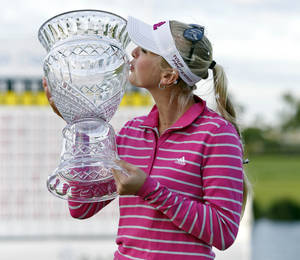 Photo - Jessica Korda of the U.S. kisses her trophy as she poses for photographers following her victory at the LPGA Pure Silk Bahamas Classic at the Ocean Club Golf Course, Paradise Island, Bahamas, Sunday, Jan. 26, 2014. (AP Photo/Tim Aylen)