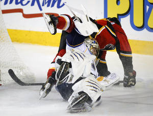 Photo - St. Louis Blues goalie Jaroslav Halak, from Slovakia, ducks as Calgary Flames' Lance Bouma dives over him during second-period NHL hockey game action in Calgary, Alberta, Monday, Dec. 23, 2013. (AP Photo/The Canadian Press, Jeff McIntosh)