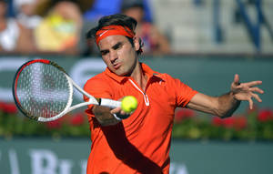 Photo - Roger Federer, of Switzerland, returns a shot to Ivan Dodig, of Croatia, during their match at the BNP Paribas Open tennis tournament, Monday, March 11, 2013, in Indian Wells, Calif. (AP Photo/Mark J. Terrill)