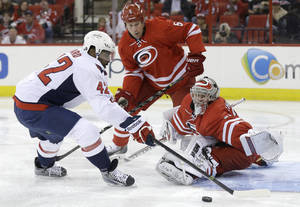 Photo - Washington Capitals' Joel Ward (42) shoots against Carolina Hurricanes goalie Anton Khudobin (31), of Kazakhstan, during the first period of an NHL hockey game in Raleigh, N.C., Thursday, April 10, 2014. Ward scored on the play. Hurricanes' Mike Komisarek (5) watches the play. (AP Photo/Gerry Broome)