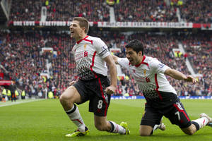 Photo - Liverpool's Steven Gerrard celebrates with teammate Luis Suarez, right, after scoring against Manchester United during their English Premier League soccer match at Old Trafford Stadium, Manchester, England, Sunday March 16, 2014. (AP Photo/Jon Super)