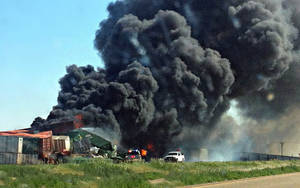 photo - Smoke rises from the scene of a train collision two miles east of Goodwell on Sunday, June 24, 2012. <strong>Trudy Hart - The Guymon Daily Herald</strong>