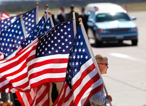 Photo - Patriot Guard Riders hold American flags near the hearse as they await the arrival of the plane carrying the remains of U.S. Army Staff Sgt. Travis Tompkins. PHOTO BY JIM BECKEL, THE OKLAHOMAN