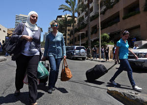 Photo - FILE - In this Thursday, June 26, 2014, file photo, tourists leave Beirut's Ramada Hotel as security forces raided some rooms in the building in Beirut. Anxiety is gripping Lebanon following a spate of suicide bombings, and an ongoing security sweep targeting militants, some of them who had been staying in four-star Beirut hotels, has triggered a wave of cancellations of hotel and flight bookings in a country already on edge. (AP Photo/Bilal Hussein, File)