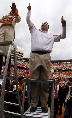 Photo - Tennessee head coach Butch Jones leads the Pride of the Southland Band after his team defeated South Carolina 23-21 in an NCAA college football game on Saturday, Oct. 19, 2013 in Knoxville, Tenn. (AP Photo/Wade Payne)
