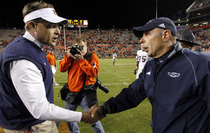Photo - Auburn head coach Gus Malzahn, left, shakes hands with Florida Atlantic head coach Carl Pelini after defeating them 45-10 in an NCAA college football game on Saturday, Oct. 26, 2013, in Auburn, Ala. (AP Photo/Butch Dill)