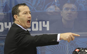 Photo - Team Canada Head Coach Kevin Dineen yells instructions to the ice during the first period of their game against Switzerland during 2014 Winter Olympics women's ice hockey game at Shayba Arena, Saturday, Feb. 8, 2014, in Sochi, Russia. (AP Photo/J. David Ake)