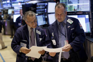 Photo - In this Tuesday, Sept. 3, 2013, photo, traders work on the floor at the New York Stock Exchange in New York. Stock futures were mixed Wednesday, Sept. 4, 2013, with the U.S. moving closer to a military confrontation in Syria (AP Photo/Seth Wenig)
