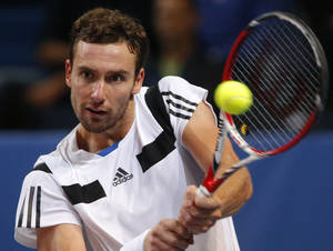 Photo - Ernests Gulbis of Latvia returns the ball to  Michal Przysiezny of Poland during the St. Petersburg Open ATP tennis tournament semi final match in St.Petersburg, Russia, Saturday, Sept. 21, 2013. (AP Photo/Dmitry Lovetsky)