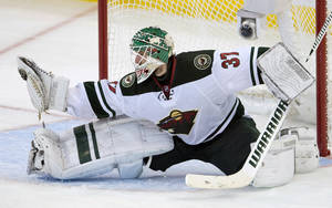 Photo - Minnesota Wild goalie Josh Harding makes a save during the second period of an NHL hockey game in Ottawa, Ontario on Wednesday, Nov. 20, 2013. (AP Photo/The Canadian Press, Adrian Wyld)