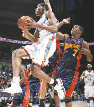 Photo - Oklahoma City's Kevin Durant, left, drives past Golden State's Kelenna Azubuike on Monday at the Ford Center. Azubuike played high school ball at Tulsa's Victory Christian. By Nate Billings, the Oklahoman