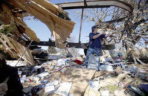 Photo - Thor Clemens cleans up tornado damage at his home, Thursday, Feb. 12, 2009, in Lone Grove, Okla. PHOTO BY SARAH PHIPPS, THE OKLAHOMAN